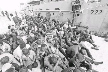??  ?? African migrants rescued from a ship off the coast of Zawiyah, about 45 kilometres west of the Libyan capital Tripoli, sit at the dock at the capital's naval base. — AFP photo