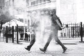 ?? RICHARD DREW/AP ?? Workers make their way through steam from a street grating during the morning commute last month in New York. Some workers are reluctant to return to the office.