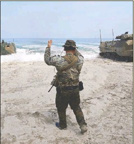 ?? KRIZJOHN ROSALES ?? A soldier signals seacraft during joint amphibious landing exercises participated in by Philippine, American and Japanese soldiers in Ternate, Cavite on Saturday.