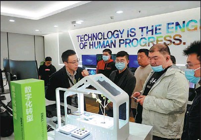?? PROVIDED TO CHINA DAILY ?? A Dell employee (second from left) fields visitors' queries during a high-tech expo in Beijing.