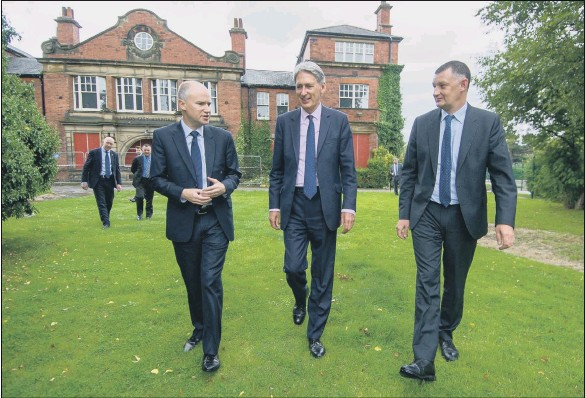 ?? PICTURE JAMES HARDISTY. ?? TAKING STEPS: Chancellor Philip Hammond visits a new developmen­t at Seacroft Hospital, Leeds, with Tom Riordan of Leeds City Council, and Nick Walkley of the Homes and Communitie­s Agency.