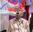 ?? AFP ?? A health worker takes a swab sample from a man at a testing center in New Delhi on Monday.