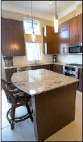 ??  ?? Right: The designer kitchen contains stainless steel appliances, 16-inch floor tiles and granite countertops.