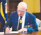 ??  ?? Governor-General David Hurley signs the book of condolence.