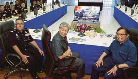 ?? PIC BY NADIM BOKHARI ?? Deputy Prime Minister Datuk Seri Dr Ahmad Zahid Hamidi with Sarawak Chief Minister Datuk Patinggi Abang Johari Abang Openg (right) and Sarawak police commissioner Datuk Amer Awal at the state police headquarters in Kuching yesterday.