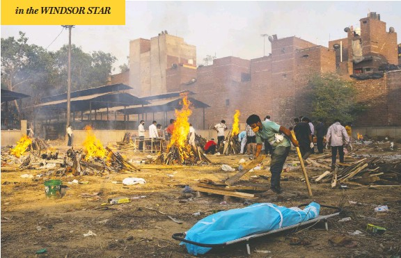 ?? DANISH SIDDIQUI / REUTERS ?? A man prepares a funeral pyre to cremate the body of a coronavirus victim at a crematorium ground in New Delhi, India, on Thursday, as cases spiked on the subcontinent.