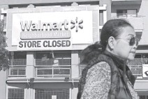 ?? MARK RALSTON, AFP/GETTY IMAGES ?? A woman walks past a recently shuttered Walmart in Los Angeles' Chinatown last month. This year, Walmart announced it would close 154 U.S. stores.