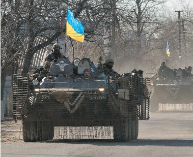 ?? VADIM GHIRDA/The Associated Press ?? Ukraine government forces drive armoured personnel carriers to a front line position east of the Sea of Azov port city, Mariupol, Ukraine, on Tuesday. The bulk of continued unrest along the 485-kilometre front line between government forces and...