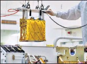 ?? REUTERS ?? Technicians lower MOXIE instrument into the belly of the Perseverance rover at a Nasa lab in Pasadena, California