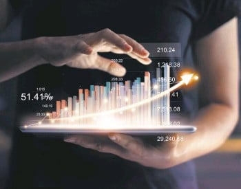 ??  ?? Businessman holding tablet and showing a growing virtual hologram of statistics, graph and chart with arrow up on dark background. Stock market. Business growth, planing and strategy concept.