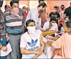 ?? AFP ?? A health worker inoculates a student with a dose of the Covishield vaccine in Amritsar.