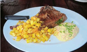 ?? Picture: JON HOUZET ?? SUCCULENT AND DELICIOUS: Tash's tomahawk steak is on special on Saturdays for R169, served with garlic mini fries and coleslaw