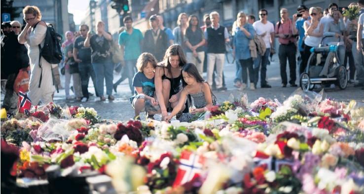 ?? Arkivbild: Björn Larsson Rosvall ?? Dagen efter dådet 2011. Osloborna hedrade minnet av offren efter vansinnesdådet genom att lägga blommor och tända ljus utanför domkyrkan.