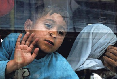 ?? SIMELA PANTZARTZI, EUROPEAN PRESSPHOTO AGENCY ?? A boy looks out of a bus window as refugees from Syria and Iraq board a bus transferring them to a new facility in Attica from the port of Piraeus, Greece, in April.