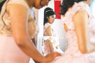 """??  ?? Ashley's mother, Griselda Rubio, helps with her dress at their home in Sterling. Growing up, Rubio's family could not afford a quinceañera. """"But she has it now,"""" Ashley said during her own celebration."""