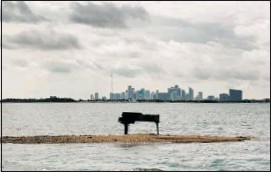 ?? Joe Raedle, Getty Images ?? A baby grand piano sits on a sandbar in Biscayne Bay near Miami. The former movie prop, now charred, was delivered there the day after a wild New Year's Eve house party.