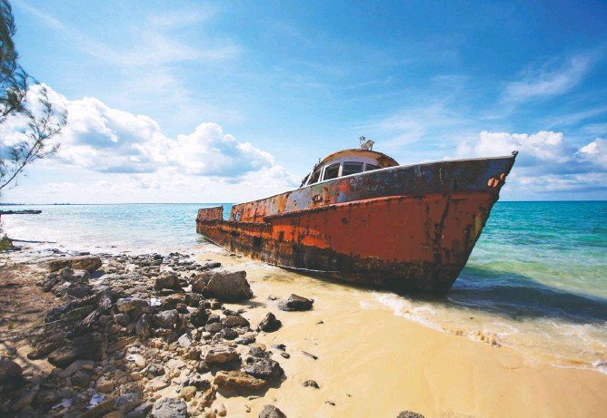 ?? PHOTOS BY JOHN BRILEY ?? TOP: A rusted-out fishing boat — the lingering legacy of its late captain — rests on the beach of Exuma Sound on Cat Island in the Out Islands of the Bahamas. ABOVE: Guide Pauline Vaz Branco, 34, swims out of a cut in a reef wall off of Cat Island, a diver's fantasy with almost no competition for dozens of prime sites.