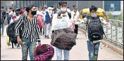 ??  ?? Migrant workers arrive at Anand Vihar Bus Terminal to leave for their hometown in New Delhi on Tuesday.