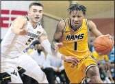 ?? DAVE EGGEN/ INERTIA ?? VCU freshman Ace Baldwin ( 1) drives past West Virginia defender Jordan McCabe during the Bad BoyMowers Crossover Classic in Sioux Falls, S. D. Baldwin recorded six assists in the Rams' defeat.