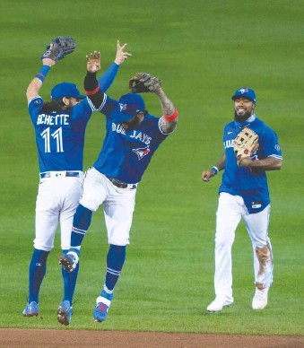 ?? GREGORY FISHER/ USA TODAY SPORTS FILES ?? Toronto Blue Jays teammates, from left, Bo Bichette, Jonathan Villar and Teoscar Hernandez celebrate after beating the Yankees late last season to clinch a playoff spot.
