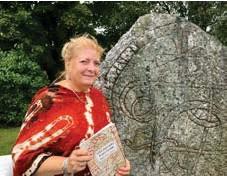 """?? FOTO: TOMAS STARK ?? VID KUMMELBYSTENEN. Anne-Berit Lavold med sin bok """"Sollentunas runstenar"""". """"Jag är lite extra stolt över att den är faktagranskad av Magnus Källström på Riksantikvarieämbetet"""", säger hon."""
