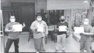 ??  ?? KAMI SEDIA: Rosli (dua kiri) menerima borang pendaftaran vaksin COVID-19 daripada Fadillah (kanan) dan ahli JKKK yang lain.