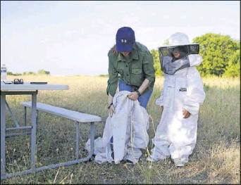 ??  ?? Ayesha Mansoor (left) of Frisco puts on a beekeeper suit during a class in Rowlett after helping daughter Yusra with hers.
