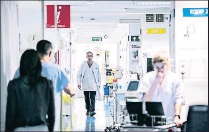 ?? XAVIER CERVERA ?? Pacientes y personal sanitario en un hospital en Barcelona