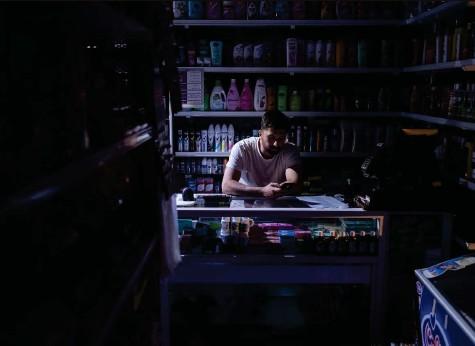 ?? Foto: Morteza Nikoubazl (Getty Images) ?? Selbst die Hauptstadt bleibt immer wieder ohne Strom: Ein Verkäufer sitzt in Teheran in seinem dunklen Laden.