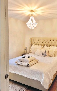 ??  ?? A wooden beaded chandelier takes prominence in the master bedroom, which has a new queen-size bed and decorative bedroom pillows and quilts.