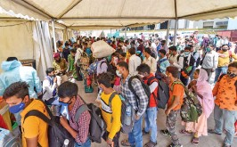 ?? — PTI ?? Passengers wait to be tested for Covid-19 at Anand Vihar bus terminal in New Delhi on Wednesday.