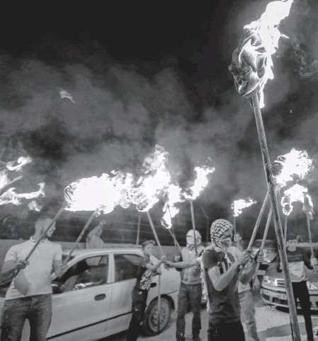 ?? MOHAMAD TOROKMAN • REUTERS ?? Palestinian demonstrators hold torches during a night protest against Israeli settlements in Beita in the Israeli-occupied West Bank on Tuesday.