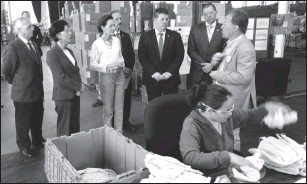 ?? Photo by Russ Olivo ?? On a tour of hte Brickle Group of textile manufacturers, city and state officials reach a section of the workshop floor where military berets are made. From left are State Sen. Marc Cote (DDist. 24), Gov. Gina Raimondo, Mayor Lisa Baldelli Hunt, State...