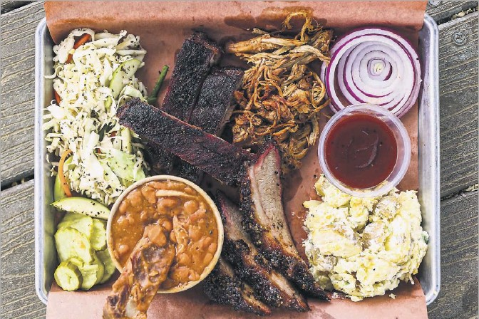 ?? Photos by Lola Gomez/staff Photographer ?? Diners can choose from meats like brisket, ribs and pulled pork, along with a variety of sides, on Bumbershoot Barbecue's three-meat plate.