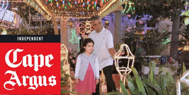 ?? TRACEY ADAMS African News Agency (ANA) ?? GRASSY Park resident Kenny Felix and his young neighbour M-yah Fernandez, 6, admire the Christmas lights he and his wife Heather have set up in their garden.