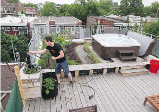 ?? JOHN KEN­NEY/MON­TREAL GAZETTE ?? Éti­enne Richer wraps up a hose af­ter tend­ing to the gar­den on a rooftop deck and gar­den at his and Élise Boyer's home in Mon­treal. They fin­ished a deck and green roof pro­ject on top of their Villeray cot­tage in 2013 for about $18,000. It al­lows them to...