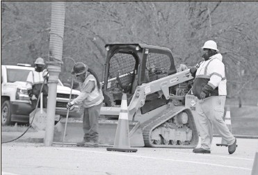 ?? Olivia Morley ?? Construction workers start slot-trenching — digging narrow trenches for the pipeline — on North Division Street on Tuesday.