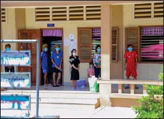 ?? PROVINCIAL HALL ?? People stand in a school that has been turned into a quarantine centre in Kampong Speu province's Chbar Mon district.