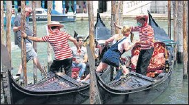 ?? REUTERS ?? Boatmen help tourists to get on gondolas as the region of Veneto was reopened to tourists following a relaxation of Covid-19 restrictions in Venice, Italy.
