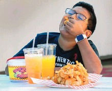?? JIM THOMPSON/JOURNAL ?? Noah Lujan of Albuquerque enjoys his food from the State Fair on Saturday.