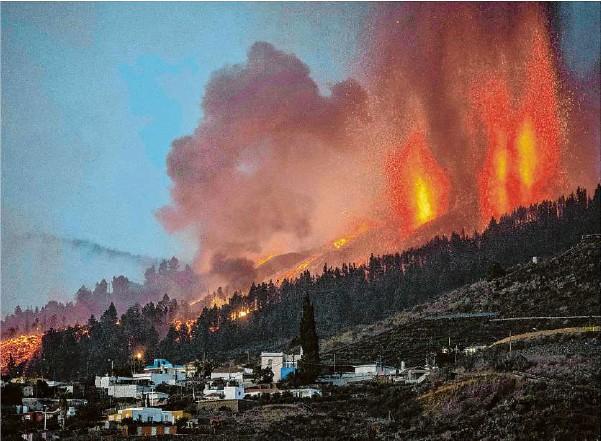 ??  ?? Der Berg Cumbre Vieja in El Paso auf La Palma spuckt Feuer, Rauch und Asche. Die Lava frisst sich durch Siedlungen. Foto Desiree Martin/afp