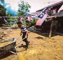 ??  ?? Penduduk membersihkan lumpur di rumahnya yang terjejas akibat fenomena kepala air