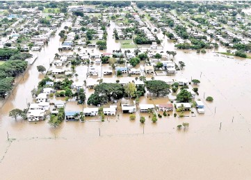 ??  ?? Houses can be seen surrounded by flood waters in the town of Ingham. — Reuters photo