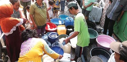 ?? WAHYU ZANUAR BUSTOMI/JAWA POS ?? SUSAHNYA DAPAT AIR: Warga Sumberejo, Kecamatan Pakal, antre air tangki dari PDAM kemarin. Pasokan berkurang, warga berebut. Sudah seminggu air mati total.