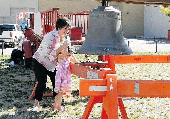 ?? SUBMITTED PHOTO ?? Debra Button and her daughter Annie ringing the Weyburn Post Office bell during the city's centennial celebration.