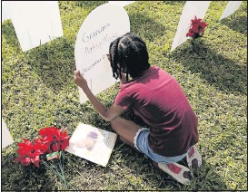 ?? THE ASSOCIATED PRESS ?? Last month, Kyla Harris, 10, wrote a tribute to her grandmothe­r Patsy Gilreath Moore, who died at age 79 of COVID-19, at a symbolic cemetery created to remember and honor lives lost to COVID-19 in the Liberty City neighborho­od of Miami.