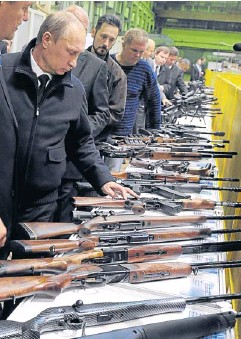 ??  ?? Russian President Vladimir Putin, left, looks at guns at the Izhevsk Machine Works factory in Izhevsk, Russia on Sept 18, 2013.