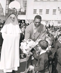 ?? Bob Campbell / The Chronicle 1964 ?? Mays receives a birthday bouquet from schoolkids while visiting Sister Eusebia (left) at St. Anthony's Immaculate Conception School in San Francisco on May 6, 1964.