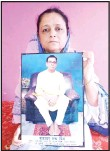 ??  ?? Anindita Mitra, 61, poses with a portrait of her husband late Narayan Mitra, at her house in Silchar, India on Sept 13. Mitra wasn't listed among those killed by the coronavirus that authorities put out daily because the test results confirming COVID-19 arrived after his death. (AP)