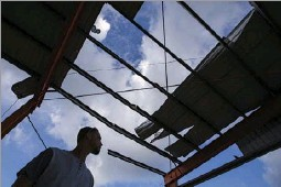 ?? Photos by Smiley N. Pool/Staff Photographer ?? Alex Claudio looks over a roof shredded by Hurricane Maria on a grandstand at a sports complex in Juncos.